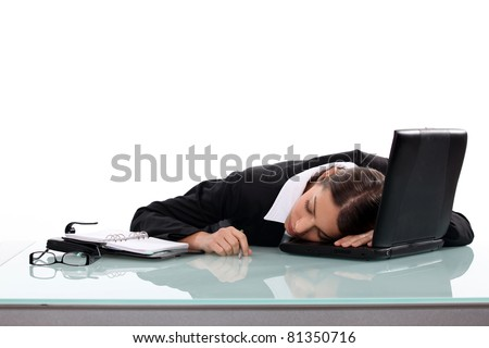 Woman asleep at her desk - stock photo
