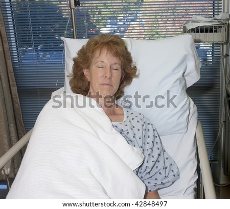 woman asleep in hospital bed - stock photo