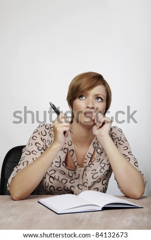 woman at a desk deep in thought - stock photo
