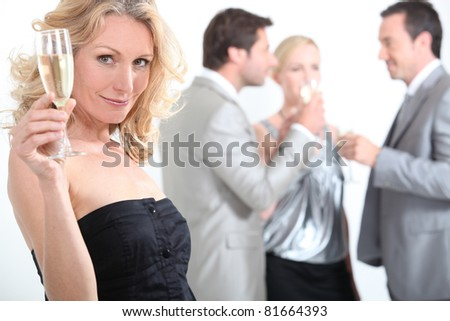 Woman at a party with a glass of champagne - stock photo