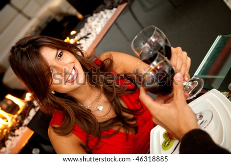 Woman at a romantic dinner toasting with a glass of wine - stock photo
