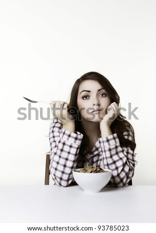 woman at a table in pajamas about to eat cereal. Please note this image has had a half colour and black and white with a sepia toning effect added. - stock photo