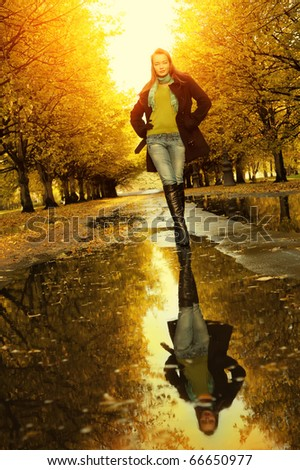 Woman at autumn outdoors walking on puddle