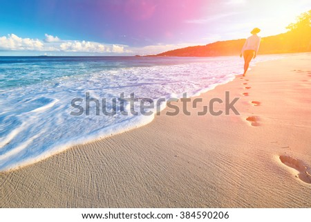 Woman at beautiful beach at Seychelles walking on sand. Focus on footprints. - stock photo