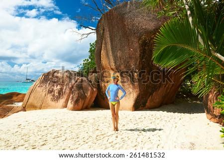 Woman at beautiful beach wearing rash guard. Seychelles, Praslin, Anse Lazio - stock photo