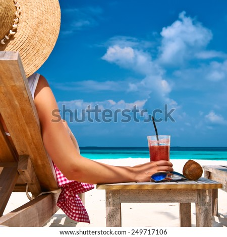 Woman at beautiful beach with chaise-lounges - stock photo