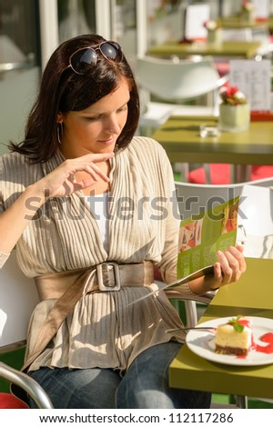 Woman at cafe bar terrace choosing from menu sunny day - stock photo