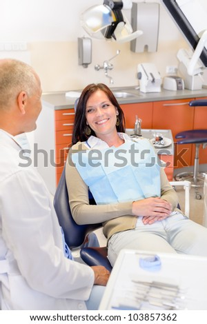 Woman at dental clinic surgery with male stomatology hygienist - stock photo