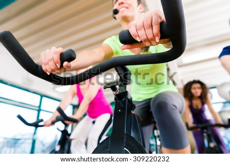 Woman at Fitness Spinning on bike in gym, shot from a low angle - stock photo