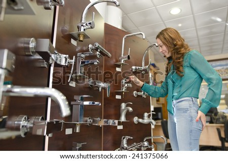 Woman at furniture and faucet store choosing for home decoration - stock photo