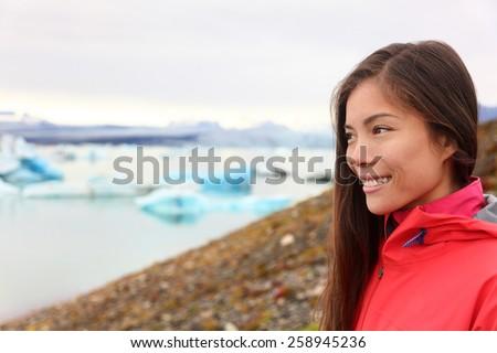Woman at glacier lagoon on Iceland. Happy tourist woman looking enjoying view of Jokulsarlon glacial lake. Smiling woman in beautiful Icelandic nature landscape looking at iceberg. - stock photo