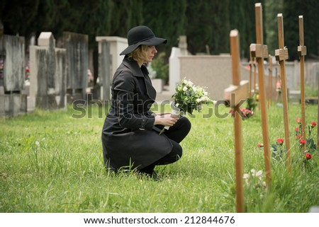 Woman at graveside with flowers - stock photo