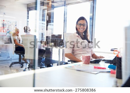 Woman at her desk in an office smiling to camera