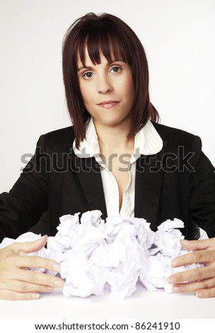 woman at her desk with screwed up paper balls - stock photo