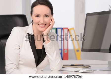 Woman at her working place. Beautiful middle-aged businesswoman sitting at her working place looking at camera and holding her hand on the chin