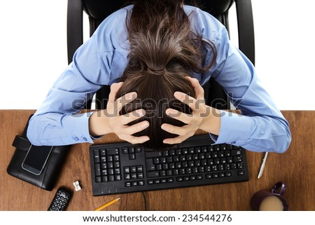 woman at hers desk not looking happy shot from a birds eye view - stock photo