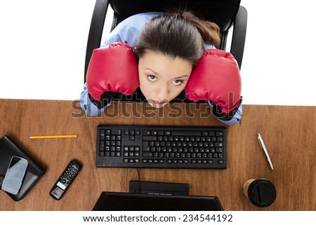 woman at hers desk wearing boxing gloves not looking very happy, shot from a birds eye view looking down - stock photo