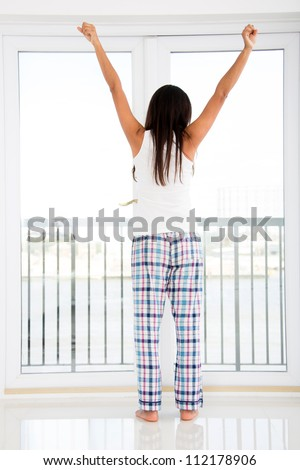 Woman at home just waking up and looking through the window - stock photo