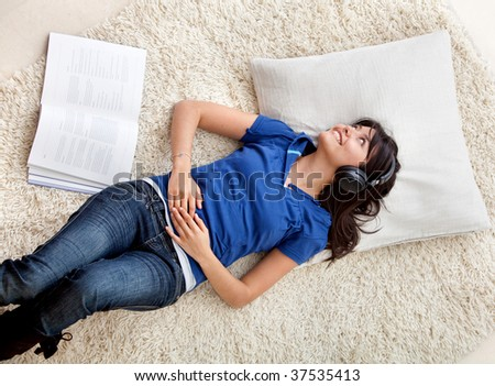 Woman at home lying on the floor listening to music - stock photo