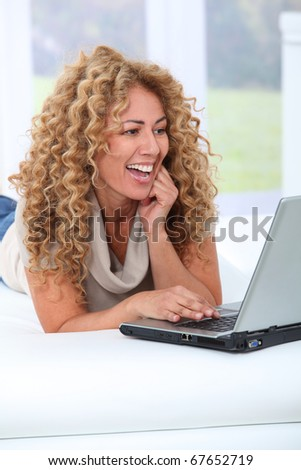 Woman at home using laptop computer - stock photo