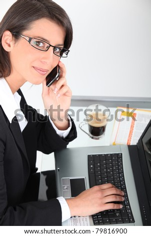 Woman at laptop with coffee and cellphone - stock photo