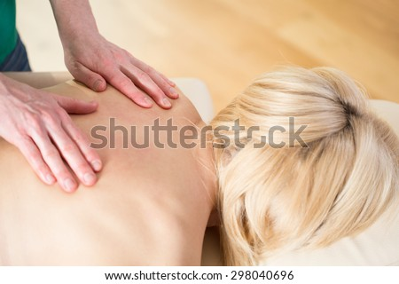 Woman at physiotherapist's office having massage - stock photo