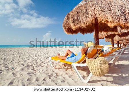 Woman at relaxation under parasol at Caribbean Sea - stock photo
