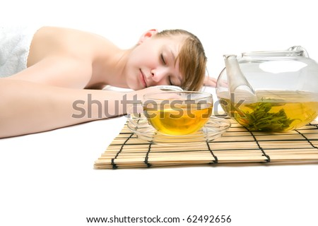 Woman at spa procedures with teapot and a cup of a green tea