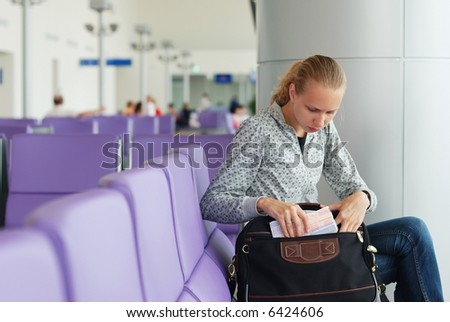 Woman at the airport witn tickets, shallow DOF - stock photo