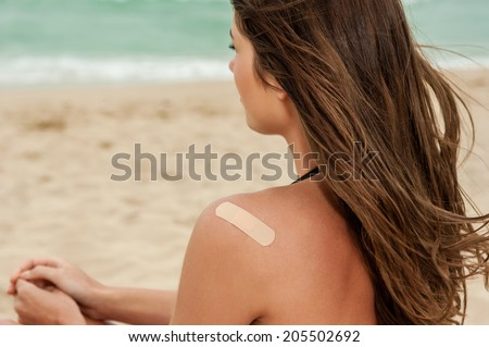 Woman at the beach with a on bandage her upper back. - stock photo