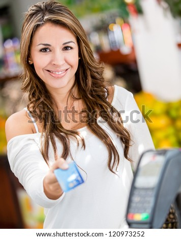 Woman at the checkout paying by credit card - stock photo