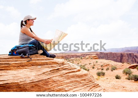 Woman at the Grand Canyon holding a map - stock photo