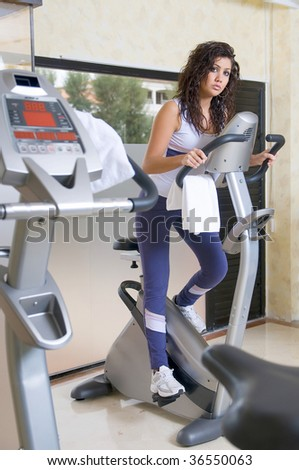 woman at the gym doing cardio bicycle exercises - stock photo