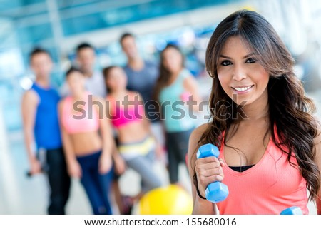 Woman at the gym lifting weights and looking happy - stock photo