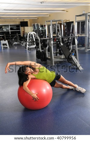 Woman at the gym stretching over fitness ball