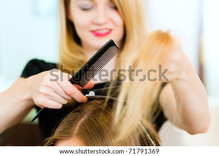 Woman at the hairdresser, she is cutting - close-up with selective focus on her hands