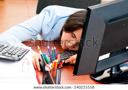 Woman at the office sleeping at workplace on the table