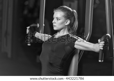 Woman at the sport gym doing arms exercises on a machine. Black and white sport club. - stock photo