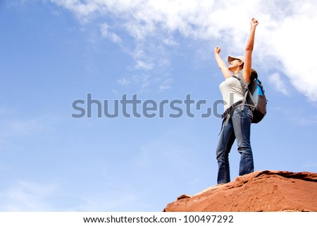 Woman at the top of a mountain conquering the world - stock photo