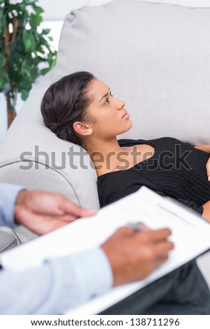 Woman at therapy session lying on sofa - stock photo