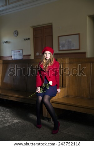 Woman at train station with rose at hand - stock photo