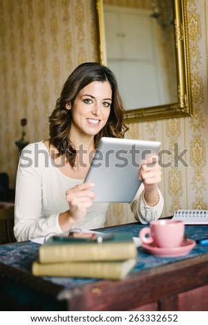 Woman at vintage looking home working and reading on digital tablet. Female young worker or student doing her job in retro desk. - stock photo