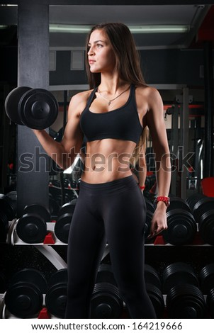 woman athlete in the gym holding a dumbbell - stock photo