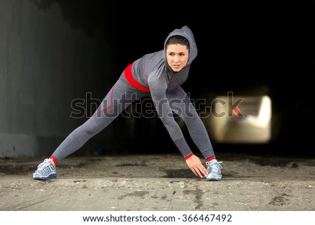 Woman athlete runner stretching her legs in city urban tunnel exercise gear and sneakers showing strength - stock photo