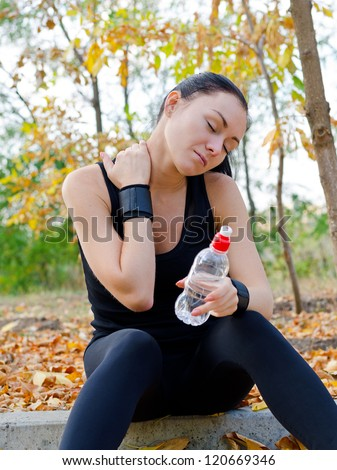 Woman athlete sitting on a curb in a park stretching her neck muscles and massaging them with her hand as she pauses for a drink of water - stock photo