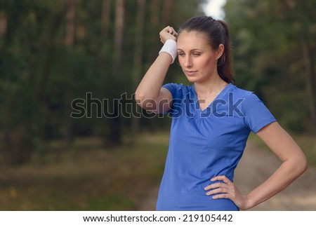Woman athlete wiping sweat from her forehead onto her wristband as she pauses during her training exercises on a forest track - stock photo