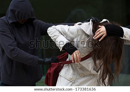 Woman attacked by a bandit, who wants to steal her purse - stock photo