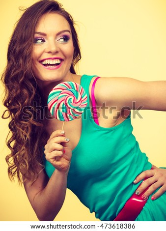Woman attractive joyful girl holding colorful lollipop candy in hand having fun. Sweet food and happiness concept. Studio shot on bright toned image
