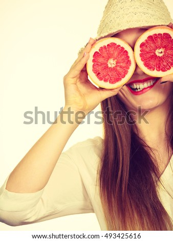 Woman attractive long hair girl covering eyes with two halfs of grapefruit citrus fruit. Healthy diet food. Summer holidays fun concept, toned image