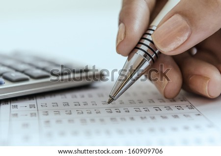 Woman auditing data printout with calculator - stock photo